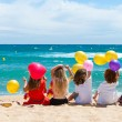Children sitting on beach with color balloons. — Stock Photo
