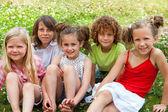 Niños sentados juntos en el campo de flor. — Foto de Stock