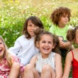 Kids sitting together in field. — Stock Photo
