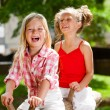 Two girl friends having great time in playground. — Stock Photo