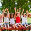 Stock Photo: Happy kids raising hands outdoors.