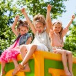 Happy girls raising arms together in park. — Stock Photo