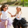 Two girls running with fantacy dresses in park. — Stock Photo #29317531