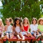 seis niños sentados juntos en la azotea en el parque — Foto de Stock