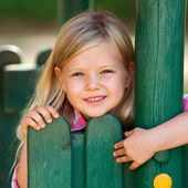 Cute girl holding on to wooden fence. — Stock Photo