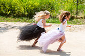 Two girls running together in park. — Stock Photo