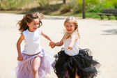 Two girls running with fantacy dresses in park. — Stock Photo
