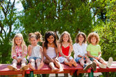 Six kids sitting together on rooftop in park. — Stock Photo
