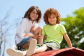 Two boys sitting on rooftop in park. — Stock Photo