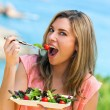 Attractive woman eating green salad. — Stock Photo