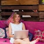 Carino biondo rilassante con il portatile sul divano — Foto Stock