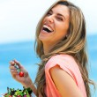 Laughing girl eating fresh salad outdoors. — Photo