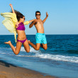 Crazy couple jump on beach. — Stock Photo