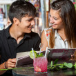 Young couple with restaurant menu at table. — Stock Photo