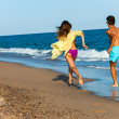 Teen couple chasing on beach. — Stock Photo