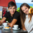 Cute teen girl showing donut at breakfast. — Stock Photo