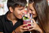 Teen couple sharing cocktail. — Stock Photo