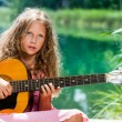 Young guitar student playing at lake. — Stock Photo