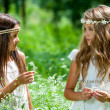 Two girls standing in flower field. — Stock Photo