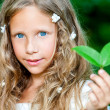 Blue eyed girl holding green leaf. — Stock Photo
