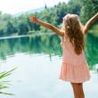 Girl standing at lakeside with open arms. — Stock Photo #33116377