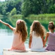 Three girl friends together on river jetty. — Stock Photo