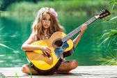Young girl with spanish guitar on jetty. — Stock Photo