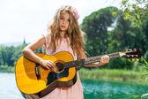 Ładny dziewczyna gra na gitarze w jeziorze. — Zdjęcie stockowe