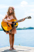 Cute girl standing with guitar at lake. — Stock Photo