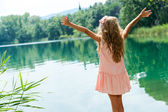 Girl standing at lakeside with open arms. — Stock Photo