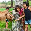Three girls feeding pony on farm. — Stock Photo