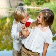 Boy surprising girl with flower. — Stock Photo
