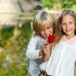 Cute teen boy giving rose to girlfriend. — Stock Photo