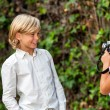 Girl taking pictute of boy outdoors. — Stock Photo