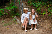 Boy and girl sitting on log in woods. — Stock Photo