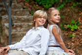 Kid couple sitting together on stairs outdoors. — Stock Photo