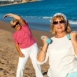 Senior female fitness session on beach. — Stock Photo