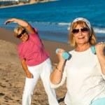 Senior female fitness session on beach. — Stock Photo