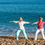 Senior ladies doing yoga on beach. — Stock Photo