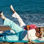 Senior women stretching legs on beach. — Stock Photo #35362691