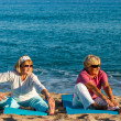 Two golden age ladies stretching on beach. — Stock Photo #35362693