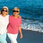 Senior female friends walking along the beach. — Stock Photo