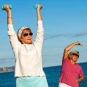 Senior ladies doing fitness exercises on beach. — Stock Photo