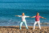 Seniors dames, faire du yoga sur la plage. — Photo