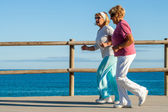 Golden agers running at seafront. — Stock Photo