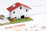 Small toy house on real estate documents. — Stock Photo