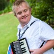 Handicapped boy playing the accordion. — Stock Photo