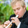 Handicapped boy playing block flute. — Stock Photo