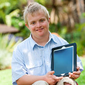 Handicapped boy holding tablet outdoors. — Stock Photo