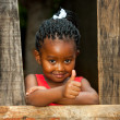 Little africgirl at wooden fence with thumbs up. — Stock Photo #38835417